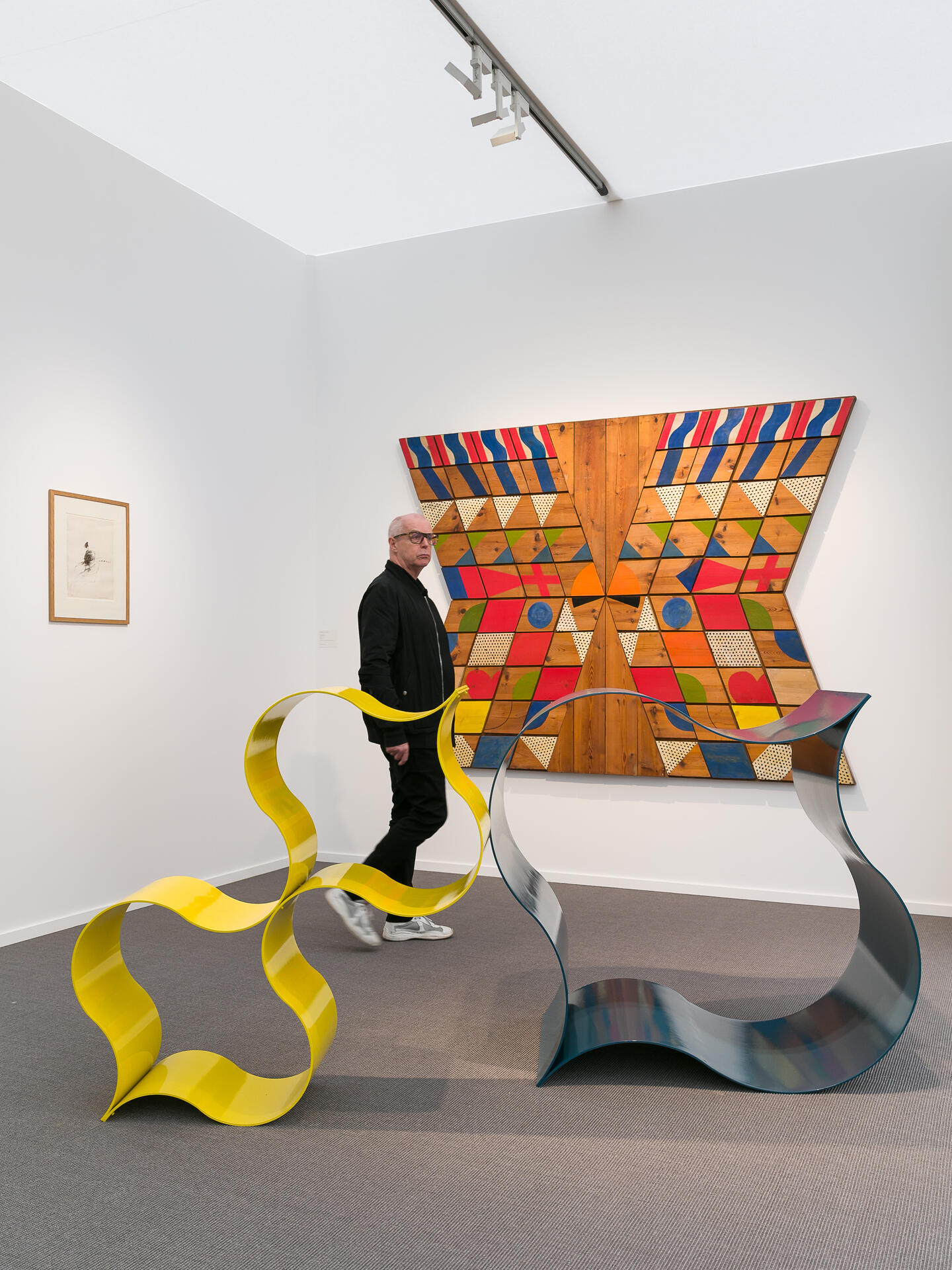 A man walking past a colourful painting and some sculptures