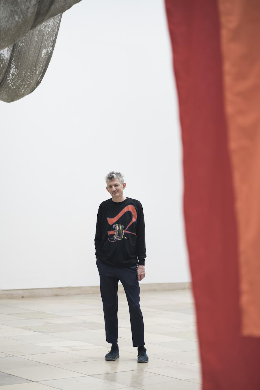 Photograph of a man stood in a gallery next to red artwork
