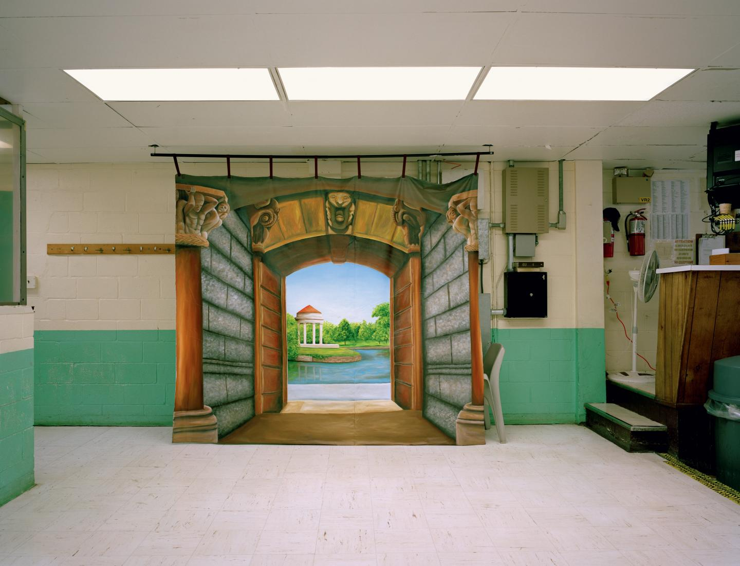 Painting of landscape with gates placed in sterile prison environment