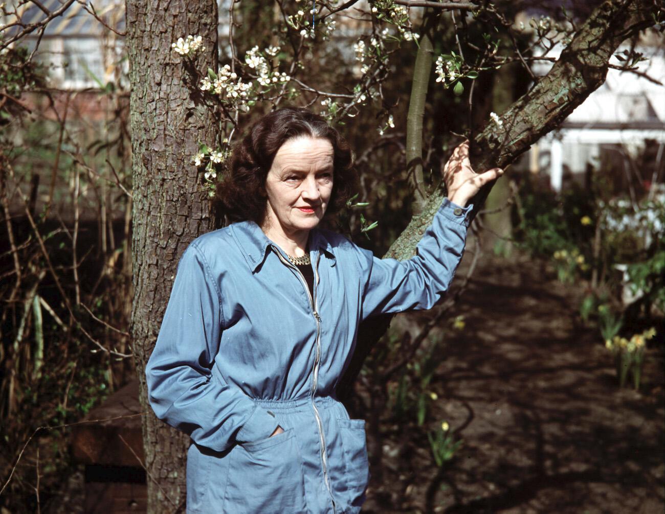 Barbara Hepworth in work jumpsuit standing next to a tree