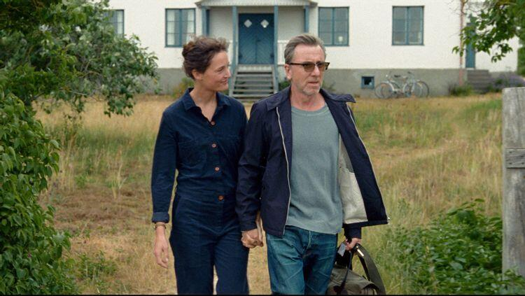 A man and a woman walk out of a house