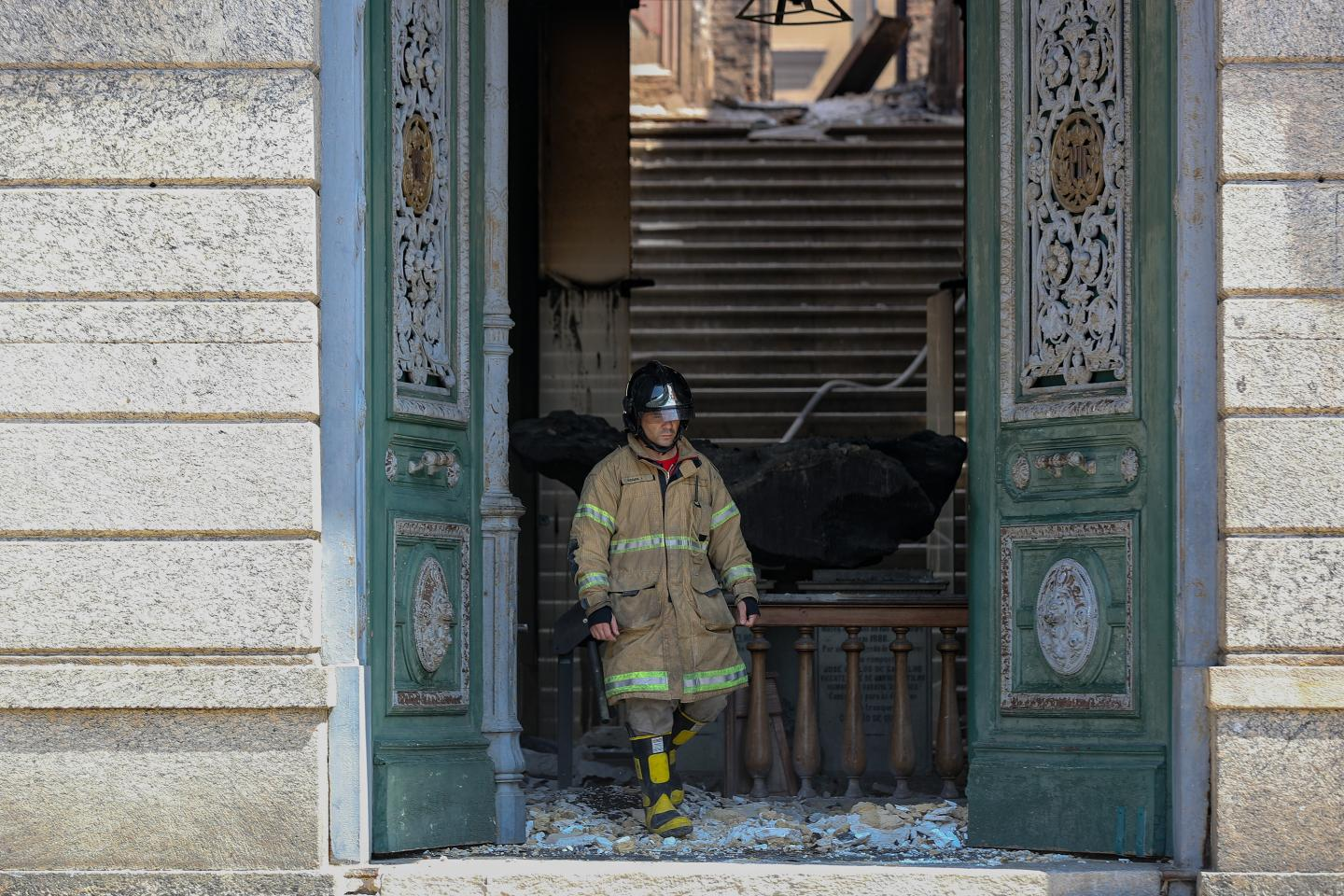 Firefighter in full uniform and equipment walking out of a burnt museum