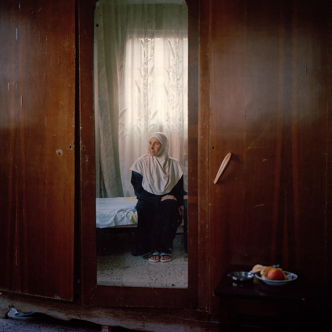 Lebanese Zahra Abbas sits on her bed in her house in Tyre, south of Lebanon. Zahra was 25 years old when her husband Mohammad went missing in 1978 as he was on his way to Lebanon from Saudi Arabia after finishing his contract there, 2014