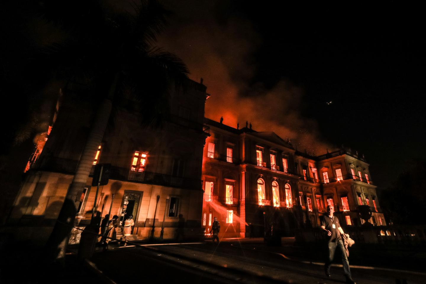 Image of museum ablaze with fire in the dark