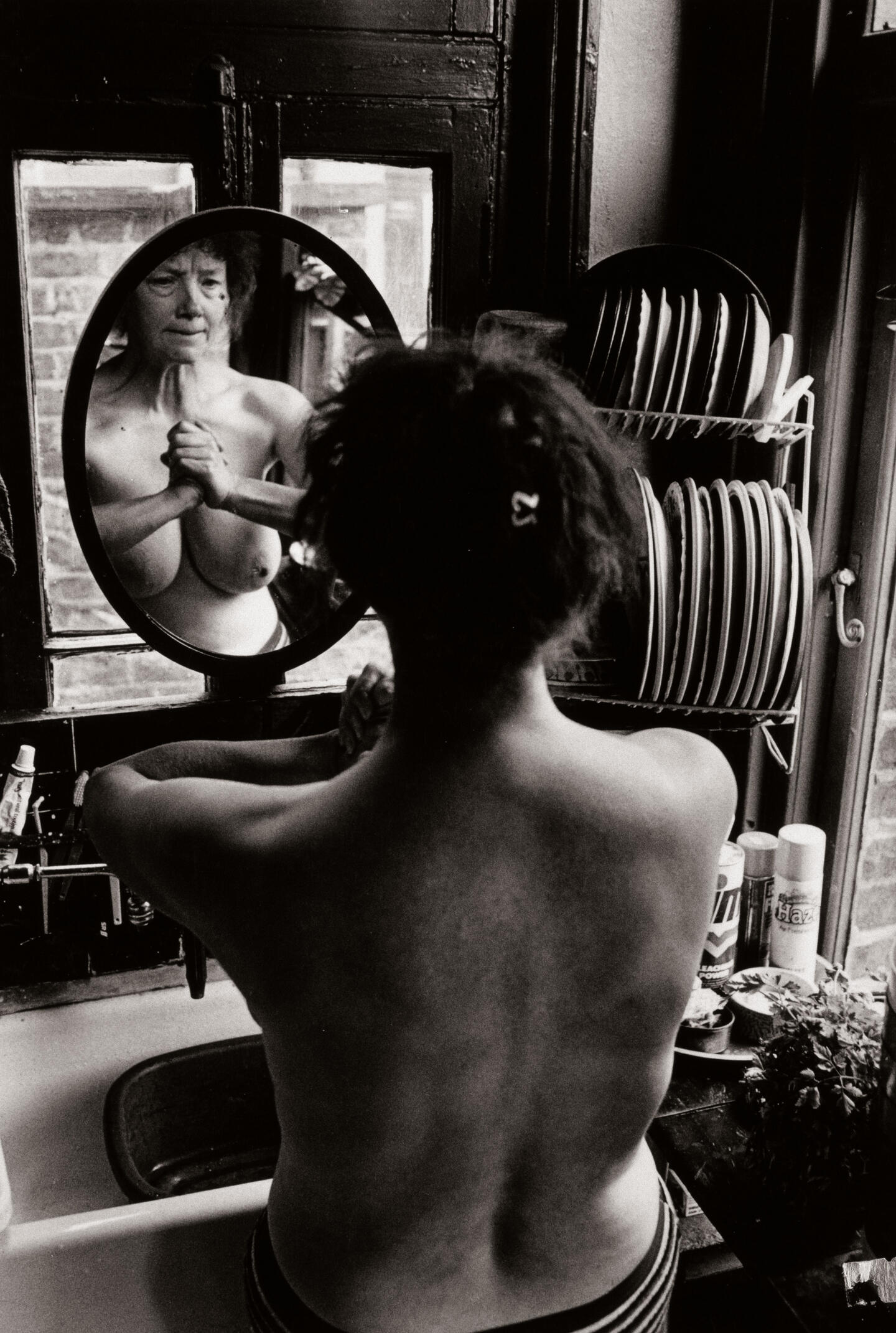 Self portrait of woman looking into mirror reflection