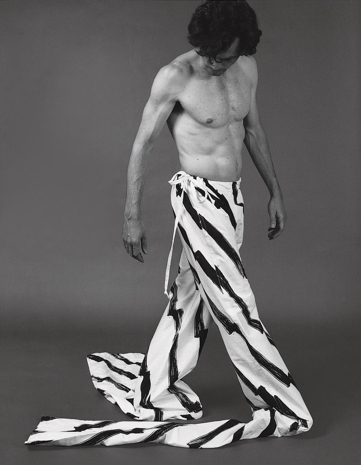 Topless man in fabric trousers, monochrome photograph