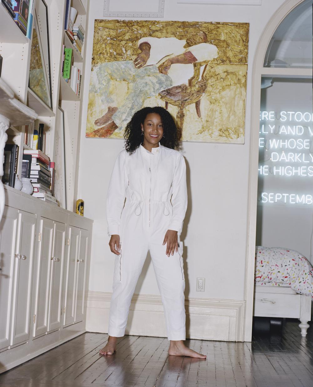 Victoria Rogers in her home. On the wall: Jennifer Packer, Mario II, 2012 Neon in the background: EJ Hill, A Commemoration, 2018 Photo:DaveyAdesida