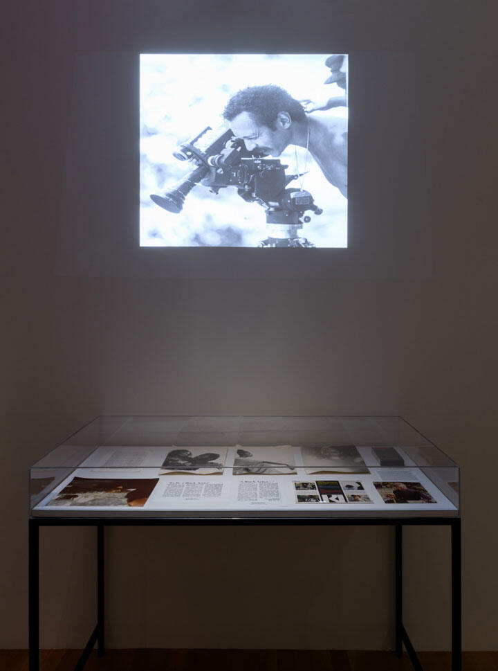 Till They Listen: Bill Gunn Directs America. Installation view, c. 1973, Artists Space, June 5 – August 15, 2021. Courtesy Artists Space, New York. Photo: Filip Wolak [An image of a projection in a dark room above a glass display case holding ephemera.]