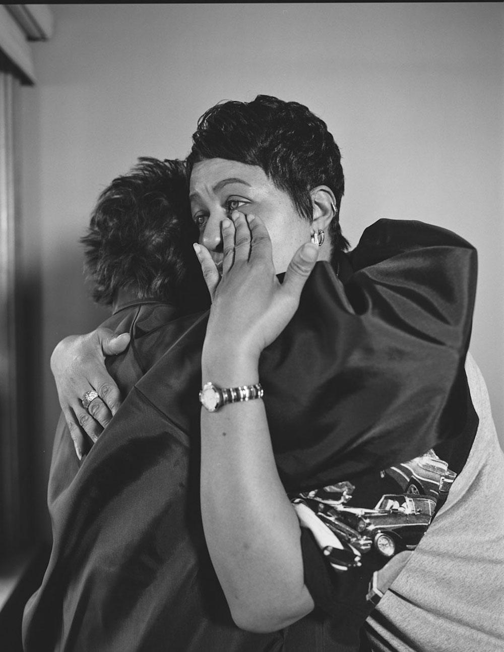 LaToya Ruby Frazier, Kesha Scales, UAW Local 1714, hugging her best friend and former co-worker, Beverly Williams, in her living room, (22 years in at GM Lordstown Complex pressroom), Youngstown, OH, 2019