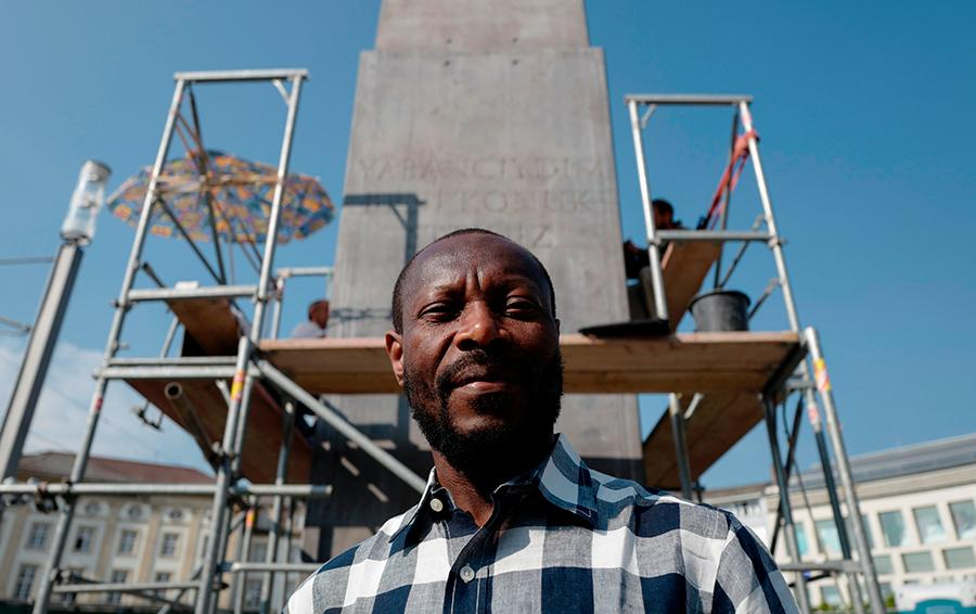 olu-oguibe-in-front-of-monument-for-refugees-strangers.