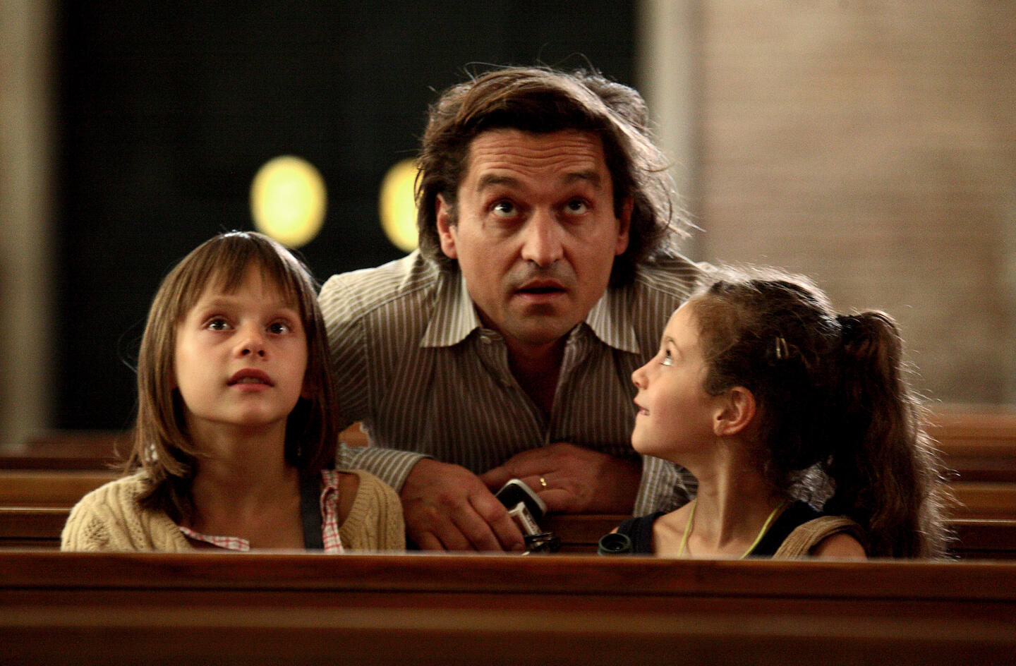 Man and children sat on a church pew