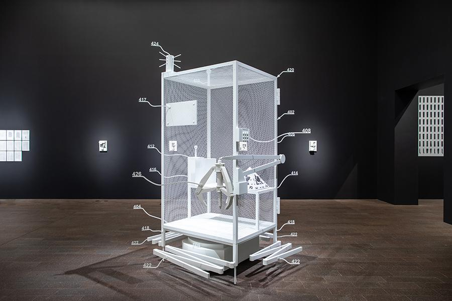"""Simon Denny, Amazon worker cage patent drawing as virtual King Island Brown Thornbill cage (US 9,280,157 B2: """"System for transporting personnel within an active workspace"""", 2016), 2019, powder-coated metal, MDF, plastic, UV print on cardboard, iOS augmented reality interface, 120 × 100 × 270 cm. Courtesy:  Studio Simon Denny"""